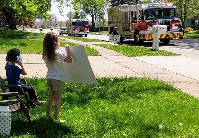 Children watching Cedar Falls Fire engine drive past